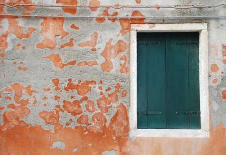 tatty: A closed green shuttered window in a wall in an historic building in Muano, Venice, Italy