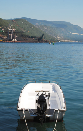 speedboats: A small white speedboat in the waters of Bakar bay in western Croatia. The industrial mining industry area can be seen in the background.