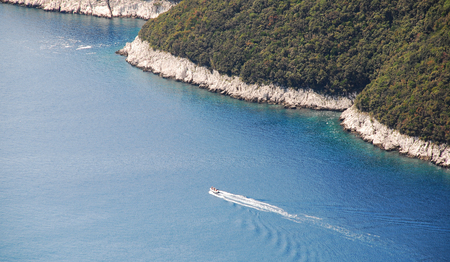 though: A small boat speeds though the beautiful clear blue waters and past the forested hills of the Croatian coast. This is the east coast of Istria, near Plomin.