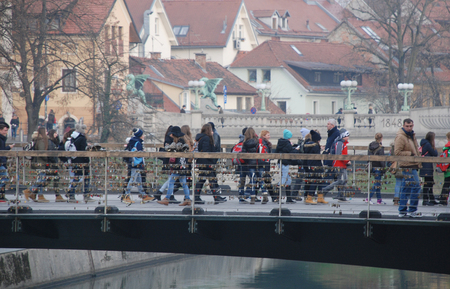 symbolize: Ljubljana, Slovenia - December 12th 2015. Passersby stop to look at padlocks on the steel wires on Mesarski Most or Butchers Bridge in central Ljubljana. The padlocks symbolize declarations of eternal love. Zmajski Most or Dragon Bridge can be seen in th