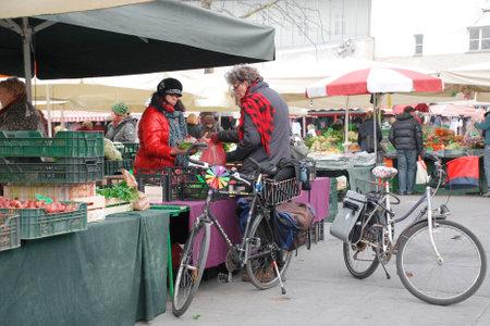 december: Ljubljana, Slovenia  December 12th 2015.  Stallholders serve customers on a cold December day at Ljubljanas Central fruit and vegetable market.