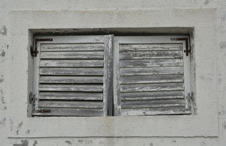 tatty: A window in an old building in the historic tiny harbour of Trsteno in Dubrovnik�??Neretva County on the Croatian coast. Stock Photo