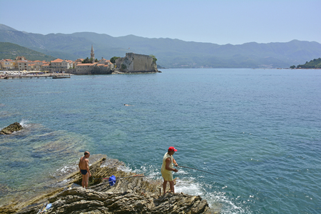 waterscapes: Budva, Montenegro - June 22nd 2016. Fishemen fish off the rocks in Budva. The old town, stari grad, can be seen in the background.