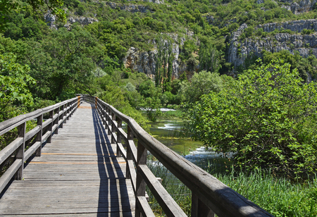 waterscapes: A wooden walkway across the Pearl Necklaces cascade on the River Krka in Krka National Park, Sibenik-Knin County, Croatia.