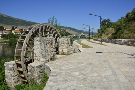 waterwheel: One of the many old water wheels on the Trebisnjica River as it flows through the town of Trebinje in southern Bosnia. The historic 16th century Ottoman Arslanagica Most bridge can be seen in the background.