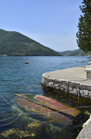 upturned: An old abandoned wooden boat, upturned and forgotten about in the harbour of the historic Montenegrin town of Perast