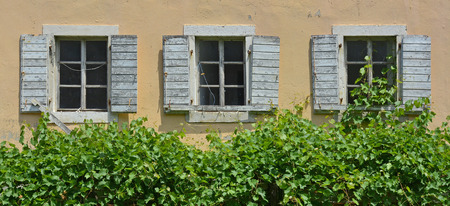 tatty: Shuttered windows in an old building in the historic Montenegrin town of Budva. Stock Photo