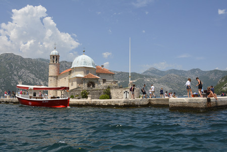 ou: Perast, Montenegro - June 27th 2016. Tourists visit the tiny man-made island of Ou Lady of the Rock, off the coast of Perast in Kotor Bay, at the stat of the tourist season.