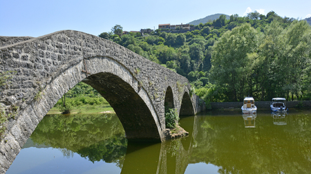metre: The old bridge in Rijeka Crnojevica, Montenegro, also known as Danilos Bridge or Danilov Most, was built across the Crnojevica River in 1853 to replace an earlier wooden bridge. The 43 metre limestrone bridge has a double arch. Stock Photo