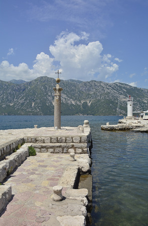 roman pillar: The Our Lady of the Rock island in Kotor Bay, Montenegro. The island was artificially created and includes a small Roman Catholic church. A cross on a stone pillar and small lighthouse can be seen in this shot