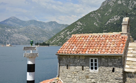 church of our lady: The historic Gospa od Andela Church - Our Lady of the Angels - in Kotor Bay, Montenegro. The church is believed to date fom 1584, and has recently been restored. Two islands - Our Lady of the Rock and St Georges Abbey - can be seen in the distance. Stock Photo