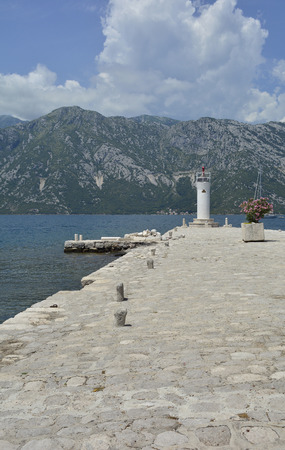 artificially: The artificially created island Our Lady of the Rock island in Kotor Bay, Montenegro. A small oleander plant can be seen in the centre right and a small lighthouse in the background