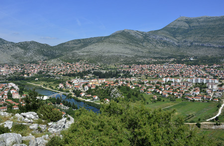 An aerial shot of the town of Trebinje in Bosnia taken from Crkvina Hill showing the historic 16th century Ottoman Arslanagica Most bridge over the Trebisnjica River. Stock Photo