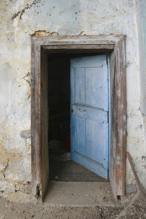 ajar: An old wooden door in a derelict building the village of Oblizza, Friuli, north east Italy.