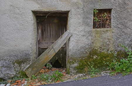 tatty: An old wooden door in a derelict building the village of Oblizza, Friuli, north east Italy.