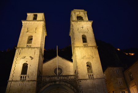 12th century: St Tryphons Cathedral in Kotor, Montenegro. Although dating back to the 12th century, the facade was destroyed and rebuilt in the 16th century following an earthquake when the baroque belltowers were also added. Kotors hillside fortifications can be seen Stock Photo