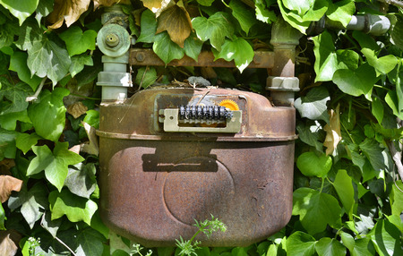 An old disused gas meter on the outside of a derelict Italian building Stock Photo