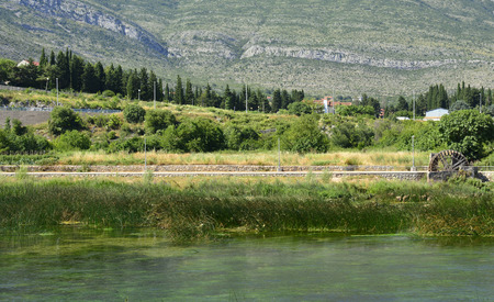 waterwheel: The Trebisnjica River as it flows through the town of Trebinje in southern Bosnia. One of the rivers many waterwheels can be seen on the right.