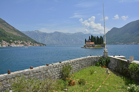 waterscapes: The tiny St Georges Island in Kotor Bay, Montenegro, also known as the Island of the Dead. The island contains a 12th century Benedictine abbey and a cemetery. The village of Perast can be seen on the coast in the background, and part of the island of Ou Stock Photo
