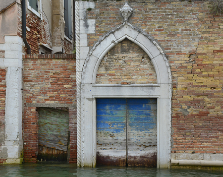 abandon: An old wooden door in a derelict building opening onto a canal in the Dorsoduro quarter of Venice