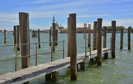 A mooring pier and mooring piles in the Dorsoduro quarter of Venice. The island of Giudecca can be seen across the Giudecca canal. The 16th century benedictine church Chiesa di San Georgio Maggiore stands out on the skyline.