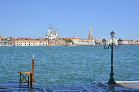 A view of the island of Dorsodoro in Venice taken from the island of Giudecca across the Giudecca Canal. The church of Santa Maria Della Salute (Saint Mary of Health) can be seen towering above the other buildings on the left, and the iconic Campanile di