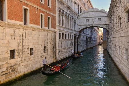 Venice, Italy - September 21 2017. Gondoliers ferry tourists around, passing under landmark the Bridge of Sighs (Ponte dei Sospiri) in Venice, Italy. Editorial