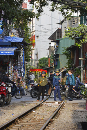 Hanoi, Vietnam - 16th December 2017. Two traffic controllers wait for signs of the 15.30 train from Hanoi to Sapa arriving in order to block road traffic to let it pass along along a residential street which is often referred to as Train Street