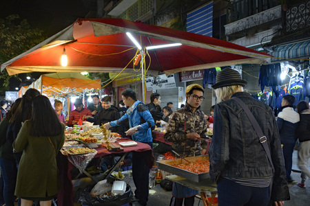 Hanoi, Vietnam - December 15th 2017. A young man serves customers at a night market stall selling local foods in the historic old quarter of Hanoi 報道画像
