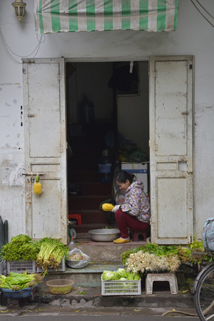 Hanoi, Vietnam - December 14th 2017. A woman prepares pineapples to sell from her home in the historic old quarter of Hanoi