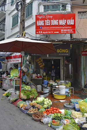 Hanoi, Vietnam - December 14th 2017. A woman waits for at a street fruit and vegetable shop in the historic old quarter of Hanoi 報道画像