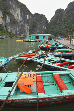 Ha Long Bay, Vietnam - December 15th 2017. Wooden tourist boats await passengers in the UNESCO listed Ha Long Bay on a overcast winter's day in low season