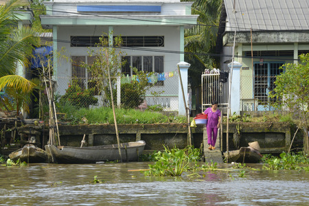 Can Tho; Vietnam - December 31st 2017. A woman walks to the river to wash some dishes in plastic tubs at the back of her house which looks out onto a waterway near Can Tho in the Mekong Delta