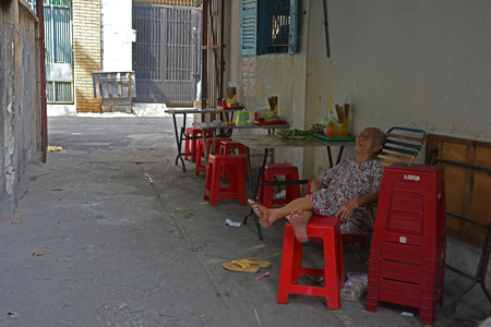 Ho Chi Minh City, Vietnam - 3rd January 2018. An elderly woman takes a nap outside a street cafe in a small back street in the Tran Hung Alleys area of District 1 in Saigon.