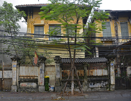 Hanoi, Vietnam - December 14th 2017. A former grand colonial house now stands in shabby disrepair in Hanoi, Vietnam