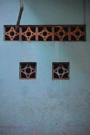 Small ventilation windows in a blue wall near Tran Hung Dao in District 1, Saigon, Vietnam