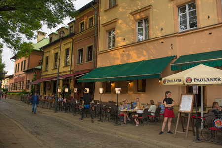 Krakow, Poland - July 9th 2018. A waitress waits for more customers outside a restaurant in the popular Krakow district of Kazimierz