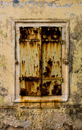 A window covered with rusty shutters in a derelict building in the Croatian hill village of Bale, also called Valle. Stok Fotoğraf