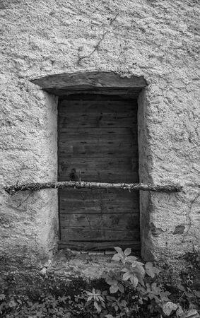 A door in a derelict stone house in the small historic hill village of Obenetto in Friuli-Venezia Giulia, north east Italy Stok Fotoğraf