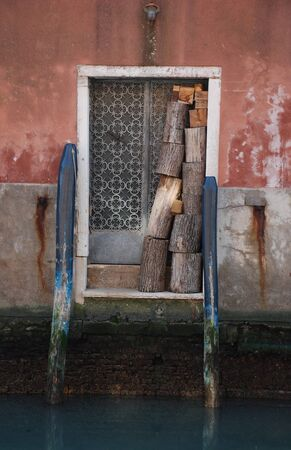 An old doorway in quiet backstreet in Venice Italy away from the crowds of tourists, Logs for burning are stacked up in the doorway
