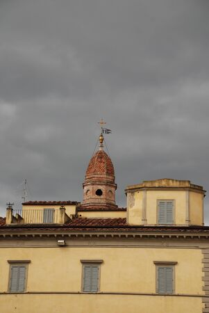 The yellow of a building is accentuated by the dark storm clouds hovering above it. Arezzo, Tuscany, Italy Stock Photo