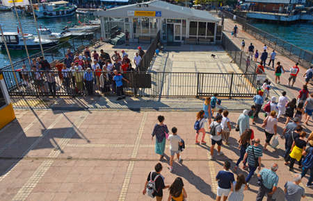 Burgazada, Turkey - September 18th 2019. Tourists disembark the ferry from Buyukada to Moda in Kadikoy, Istanbul, at the Burgazada ferry station in the Princes' Islands, also known as Adalar. More passengers await boarding behind the closed gates