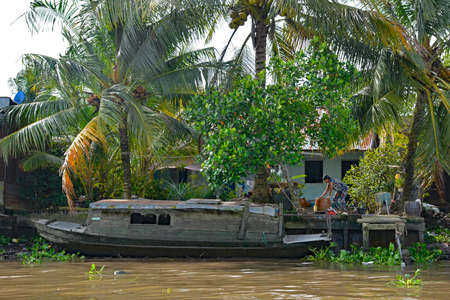 Can Tho; Vietnam - December 31st 2017. A boat moored outside a house in the Mekong Delta. A woman moves some large pots on shore in the background