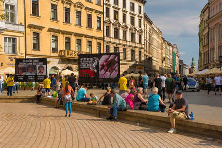 Krakow, Poland - July 13th 2018. Tourists completely ignore an anti-abortion protest in Rynek Glowny, the main square in old town Krakow. The police maintain a presence, but it isn't needed 新聞圖片
