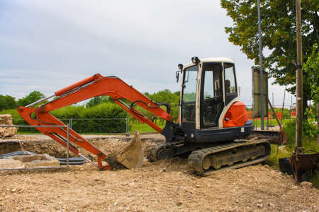 A compact crawler excavator with a rotating house platform and continuous caterpillar track on a sewer replacement work site in north west Italy
