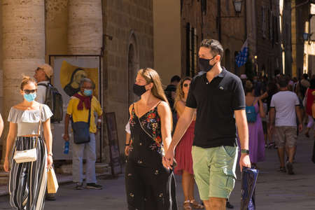 Pienza, Italy - September 6th 2020. Tourists in the historic Piazza Pio II in Pienza in Tuscany, Italy, during the COVID-19 pandemic. At this time, mask use is compulsory in the historic centre, although not everyone is complying with the rule or wearing  Editorial