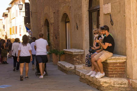 Pienza, Italy - September 6th 2020. Tourists near the historic Piazza Pio II in Pienza in Tuscany, Italy, during the COVID-19 pandemic. At this time, mask use is compulsory in the historic centre, although not everyone is complying with the rule or wearin