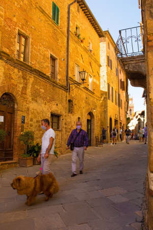 Pienza, Italy - September 6th 2020. Tourists and local residents near the historic Piazza Pio II in Pienza in Tuscany, Italy, during the COVID-19 pandemic. At this time, mask use is compulsory in the historic centre