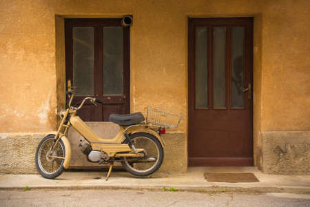 An old moped parked outside a house in a backstreet in Tolmin in the Primorska region in western Slovenia Banque d'images