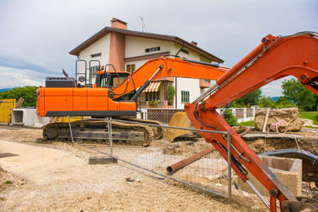 Crawler excavators with rotating house platforms and continuous caterpillar tracks on a sewer replacement work site in north west Italy